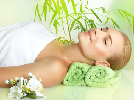 Portrait of a happy smiling woman with closed eyes of pleasure lying down on a massage table at luxury spa salon, enjoying beauty treatment and pampering