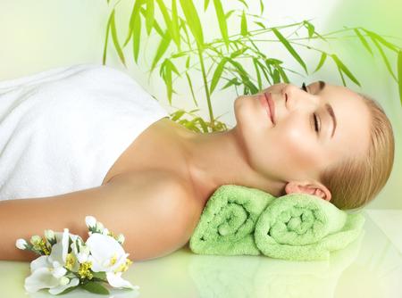 mimos: Retrato de una mujer sonriente con los ojos cerrados de placer que se acuesta en una mesa de masaje en el sal�n de spa de lujo, disfrutando de tratamientos de belleza y cuidado del cuerpo