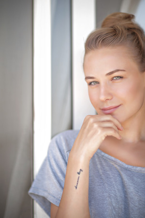authentic: Portrait of a nice blond female standing near the window at home, natural beauty, peace and harmony