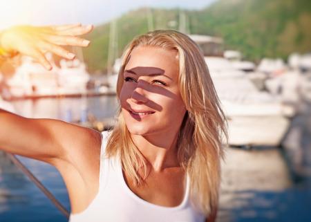 Portré egy gyönyörű szőke lány, amely arcát kezébe éles napfény, kiadások hétvégén a hajó, boldog nyári vakáció Stock fotó