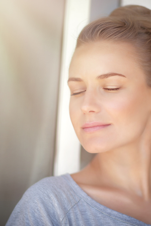 without windows: Closeup portrait of a nice female with closed eyes standing near the window at home and enjoying warm sun light Stock Photo