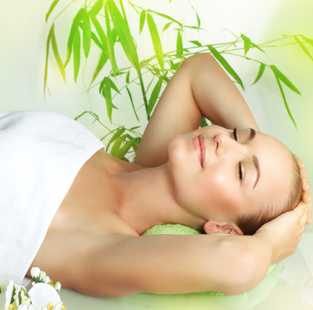 woman laying: Happy smiling girl with closed eyes lying down on massage table in a spa salon, beauty treatment, pampering and skin care