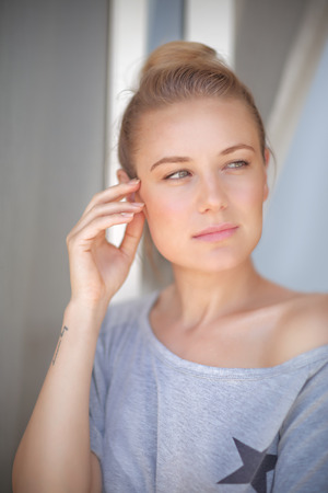 without windows: Portrait of a beautiful calm woman at home, standing near window and thinking, natural authentic beauty Stock Photo