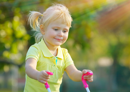 Portrait of a cute little baby girl walking with pram outdoors, happy child with toys playing in the park on a bright sunny day, preschoolers daycare photo