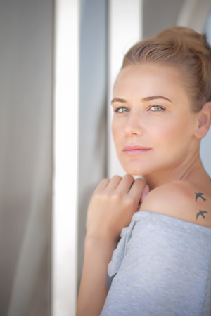 authentic: Portrait of a beautiful calm woman at home, casual gorgeous female standing near window, natural authentic beauty