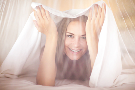 white sheet: Portrait of a happy joyful woman in the bed, playing and having fun at home, peeking out from under the sheets and looking through the tulle