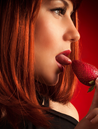 sensual lips: Profile portrait of a beautiful woman with red hair temptingly eating strawberry over red background, dessert for romantic holiday