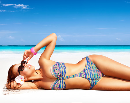 Beautiful woman on the beach, lying down on clean white sandy coast and with pleasure sunbathing, summer vacation on a tropical islands Archivio Fotografico
