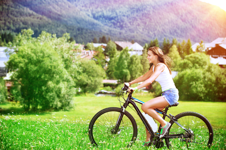 Happy sportive woman riding bicycle, active people traveling, recreation in Alpine mountains, Austria, Europe