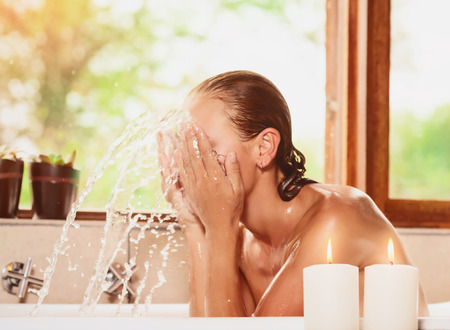 taking bath: Female washing up face and splashing water in the bathtub, healthy lifestyle, taking bath in a relaxing atmosphere at home