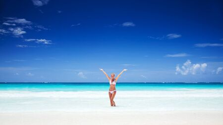 resort beach: Happy girl with raised up hands enjoying bright sunny day, spending holidays on the tropical beach resort, photo with copy space, happy summer vacation