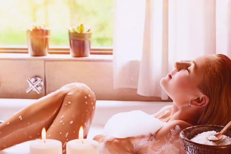 Pretty woman relaxing in the bathtub, spending peaceful time in a luxury spa resort, enjoying dayspa Stock Photo