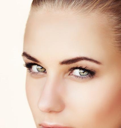 Close-up portret van een mooie vrouw gezicht met groene ogen, geïsoleerd op een beige achtergrond, aantrekkelijk model met natuurlijke make-up op perfecte huid, beauty salon