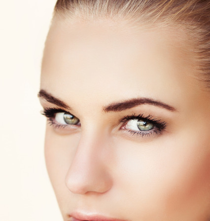 Closeup portrait of a beautiful woman face with green eyes, isolated on beige background, attractive model with natural makeup on perfect skin, beauty salon