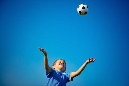 Happy boy playing ball, cute little child catching ball over blue sky background, playing football in sunny summer day, happy healthy childhood photo