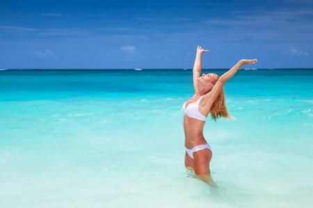 Gelukkige vrouw op het strand met opgewekt handen, genieten van zonnige dag, reizen naar de eilanden