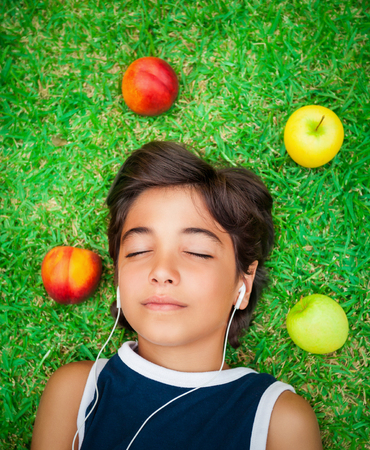 Portrait of a cute teen boy listening music, lying down on a fresh green grass field with closed eyes, relaxation outdoors