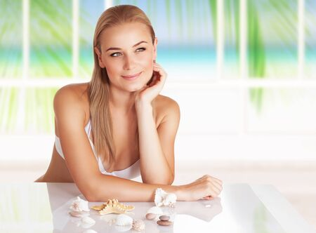 beach window: Beautiful woman relaxing on the beach resort, sitting in the house with  beautiful view to the sea and tropical nature  behind the window, enjoying summer vacation Stock Photo