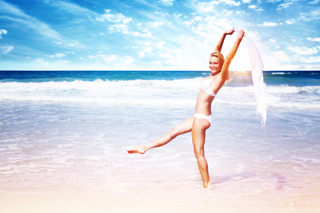Beautiful woman on the beach, attractive slim model wearing white swimsuit and dancing with a scarf, enjoying summer holidays