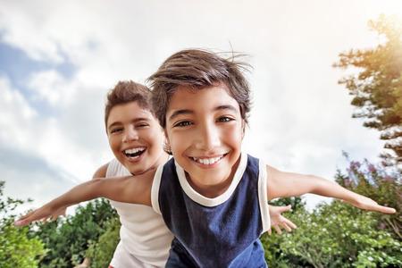 play: hermanos felices divertirse al aire libre, jugando como si volara, dos niños activos que pasan las vacaciones de verano con mucho gusto en un campo