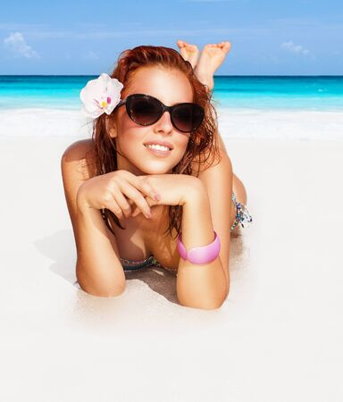 Beautiful woman on the beach, happy girl lying down on perfect white sandy coast and taking sunbath, happy summer vacation photo