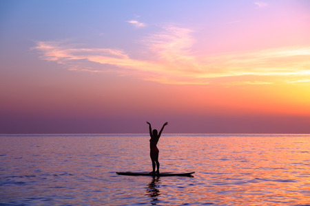 Silhouette of a yoga trainer over sunset background doing asanas, balancing on the sup board, enjoying healthy lifestyle, summer vacation on the beach Stock Photo