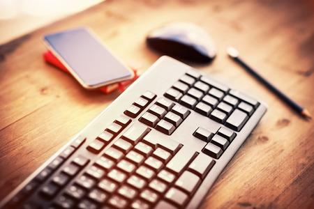 Bureau dans le bureau, clavier d'ordinateur, pc souris et téléphone mobile sur la table en bois, lieu de travail de quelqu'un Banque d'images - 62601245