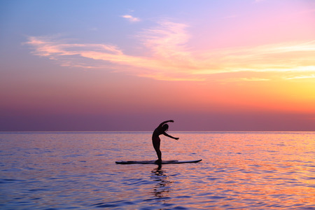 gymnastics silhouette: Silhouette of a yoga trainer over sunset background doing asanas, balancing on the sup board, enjoying healthy lifestyle, summer vacation on the beach Stock Photo