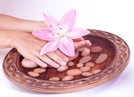 handcare: Closeup photo of a womans hand holding pink lily flower and touching pebbles in the water, isolated on clear background, hygiene and spa concept Stock Photo
