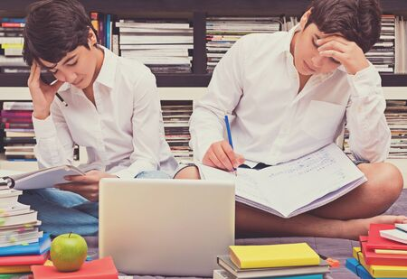 classbook: Two schoolboys sitting in the library and thinking about a difficult task, doing home work, education in the high school, back to school