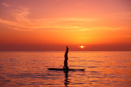 haciendo ejercicio: Silueta de un entrenador de yoga que balancea en el agua en el tablero de paleta sobre fondo naranja bella puesta de sol, de pie sobre la cabeza, haciendo Sirshasana en la playa Foto de archivo