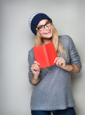 classbook: Happy student girl with book in hands wearing stylish hat and glasses isolated on gray background, enrollee of university