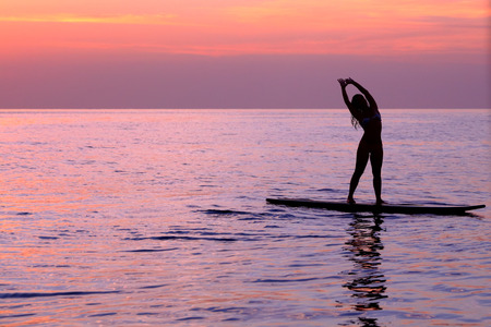 Silhouette of a girl practicing yoga, balancing on the surf board in the sea over beautiful purple sunset, healthy lifestyle and active summer vacation