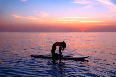 Silhouette of a yoga trainer balancing on the water on the paddle board over beautiful purple sunset background, doing yoga asana Urdhva dhanurasana on the beach