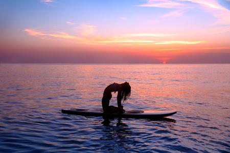 Silhouet van een yoga-trainer balanceren op het water op de paddle board over de prachtige paarse zonsondergang op de achtergrond, het doen van yoga asana Urdhva dhanurasana op het strand Stockfoto