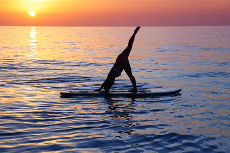 Sportive female doing yoga exercise on the beach over beautiful sunset background, standing on the sup board on the water in Pose dog muzzle down, Adho Mukha Svanasana Stockfoto