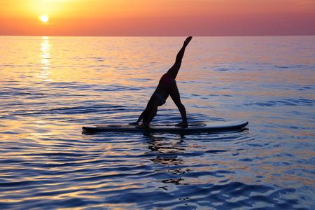 Sportive weiblichen schönen Sonnenuntergang Hintergrund macht Yoga-Übung am Strand vorbei, auf dem sup Brett auf dem Wasser in Pose Maulkorb Hund unten stehend, Adho Mukha Svanasana