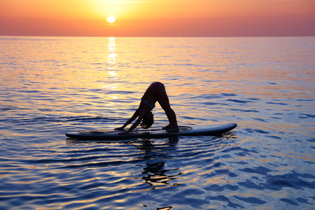 Sportive female doing yoga exercise on the beach over beautiful sunset background, standing on the sup board on the water in Pose dog muzzle down, Adho Mukha Svanasana Stock Photo