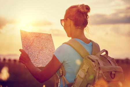 Achter mening van een reiziger meisje met rugzak verkennen kaart, profiteert van een mild zonsondergang licht, actieve mensen levensstijl, de zomer pret vakantie, reizen rond de wereld