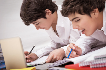 resolving: Classmates doing homework together at home, resolving difficult task, preparation to exams, with pleasure studying at school Stock Photo