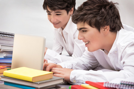 difficult task: Happy schoolboys studying, two smart friends searching information on the internet for resolving difficult home task, back to school concept