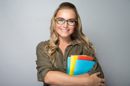 classbook: Portrait of a nice blond student girl wearing glasses, holding colorful books, shot over gray background, education in university Stock Photo