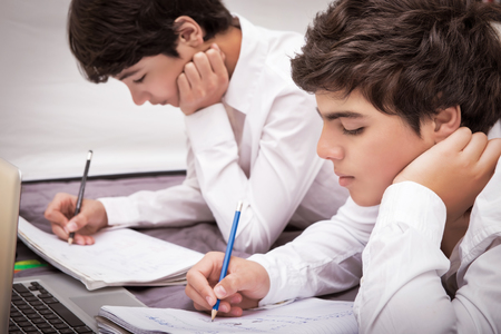 classbook: Two teenage boys doing homework at home, writing something in their notebooks, enjoying studies, education concet