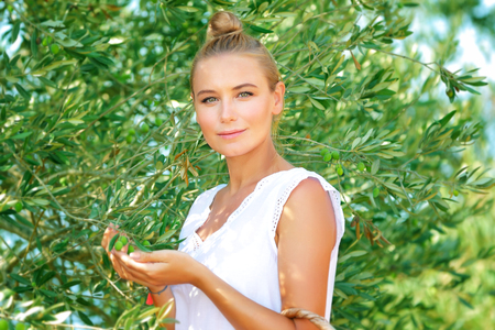 Portrait of a beautiful gentle girl enjoying olive garden, picking autumn harvest, cultivation of organic fruits, healthy life in a countryside Archivio Fotografico