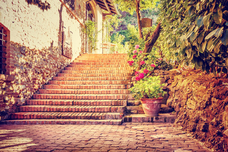 italy street: Beautiful old street, vintage stairs near house decorated with flowers and little bricks, romantic place for walking in Italy, Europe Stock Photo