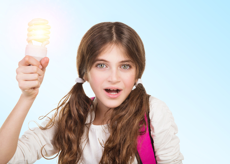 resolve: Portrait of a clever school girl with new idea, holding glowing lamp in hands, create a solution and resolve a problem concept, back to school Stock Photo