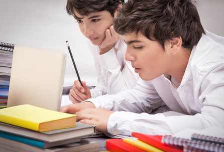 difficult task: Two classmates doing homework together at home, resolving difficult task, searching information on internet, preparation to exams, with pleasure studying at school Stock Photo