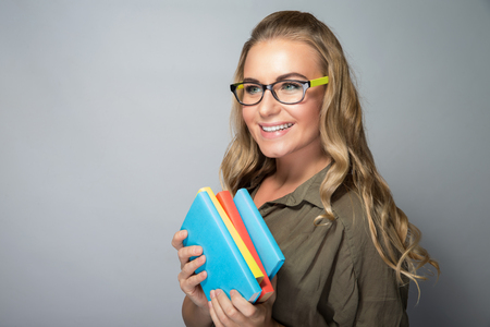 classbook: Cute student girl portrait, wearing grasses and standing with books over gray background, ready to new study season, enjoying education in a college