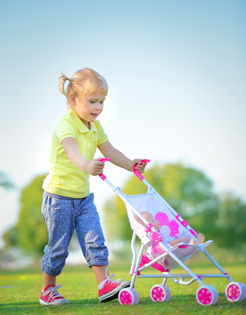 Cute little baby girl walking with pram outdoors, happy child with toys playing in the park on a bright sunny day, preschoolers daycare photo