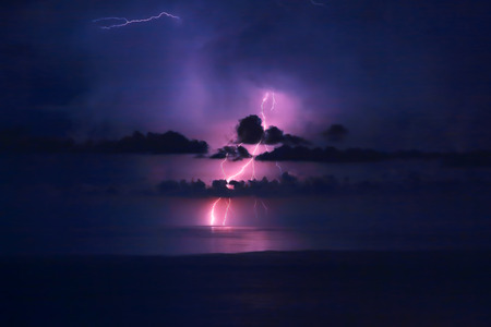 thundershower: Beautiful dramatic landscape, bright pink lightning over water, storm in the sea, autumn weather, amazing natural wallpaper Stock Photo
